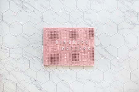 Kindness matters, be kind always. Pink pegboard on while tiles.