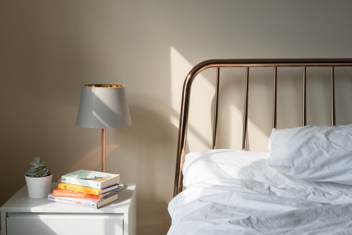 The image is focused on a desk. The desk has a lamp situated on it, with a stack of books and a fake plant as well. There is a partial view of a bed with white sheets.