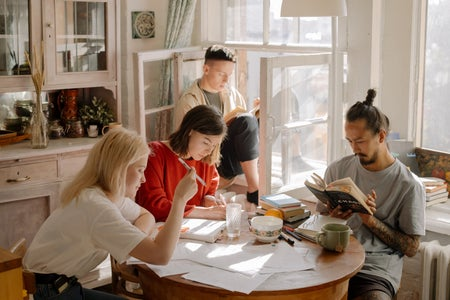 group of people studying and reading at a kitchen table