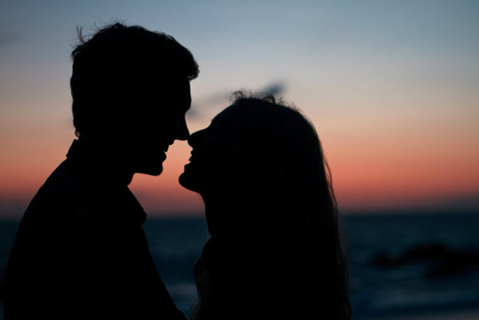 silhouette of man and woman kissing at sunset