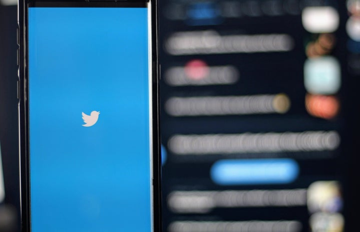 Twitter logo in front of a blurred screen