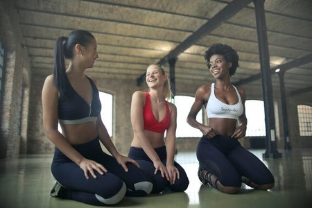 three women on the floor working out