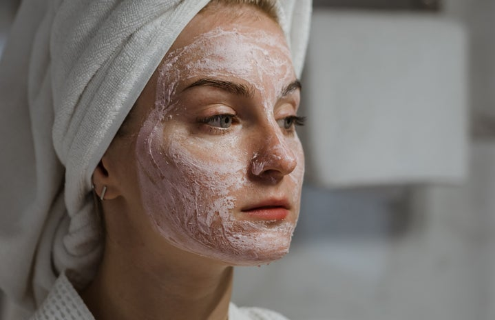 woman with white towel on head and face mask