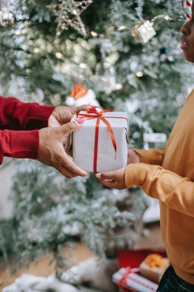 woman handing gift to child in front of christmas tree