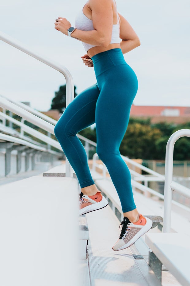 woman running up bleacher stairs