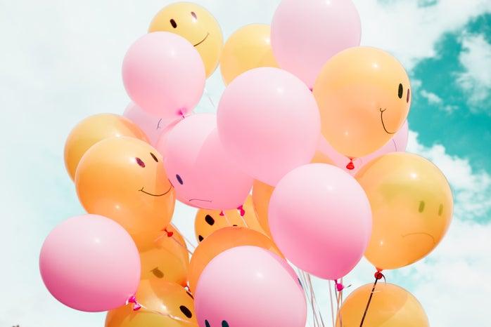 Low angle photo of pink & orange balloons