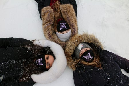 Three women laying in the snow on campus