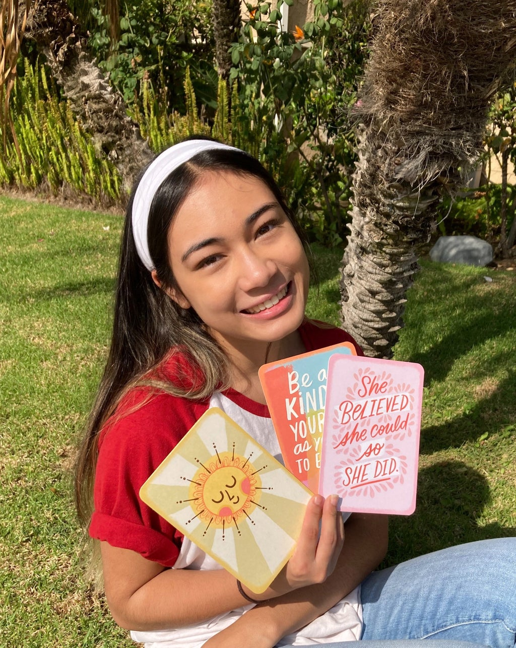 Girl holding Hallmark cards and smiling.
