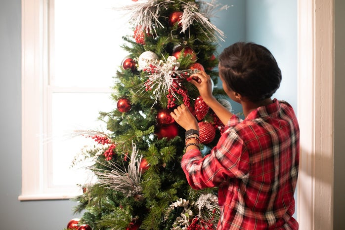 woman in red plaid shirt decorating a Christmas tree.