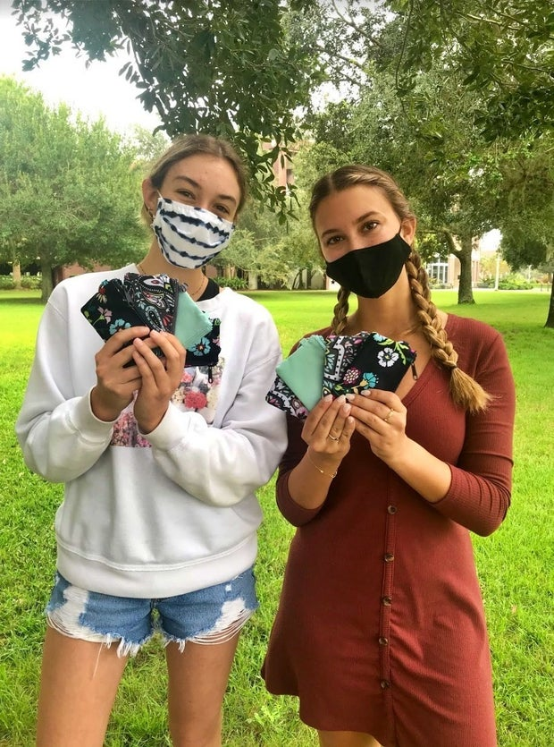 students holding wallets up to their faces