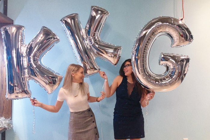 two sorority sisters holding silver KKG balloons