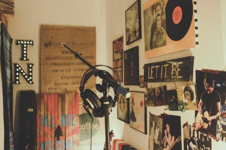 black microphone and headphones in front of poster decorated walls