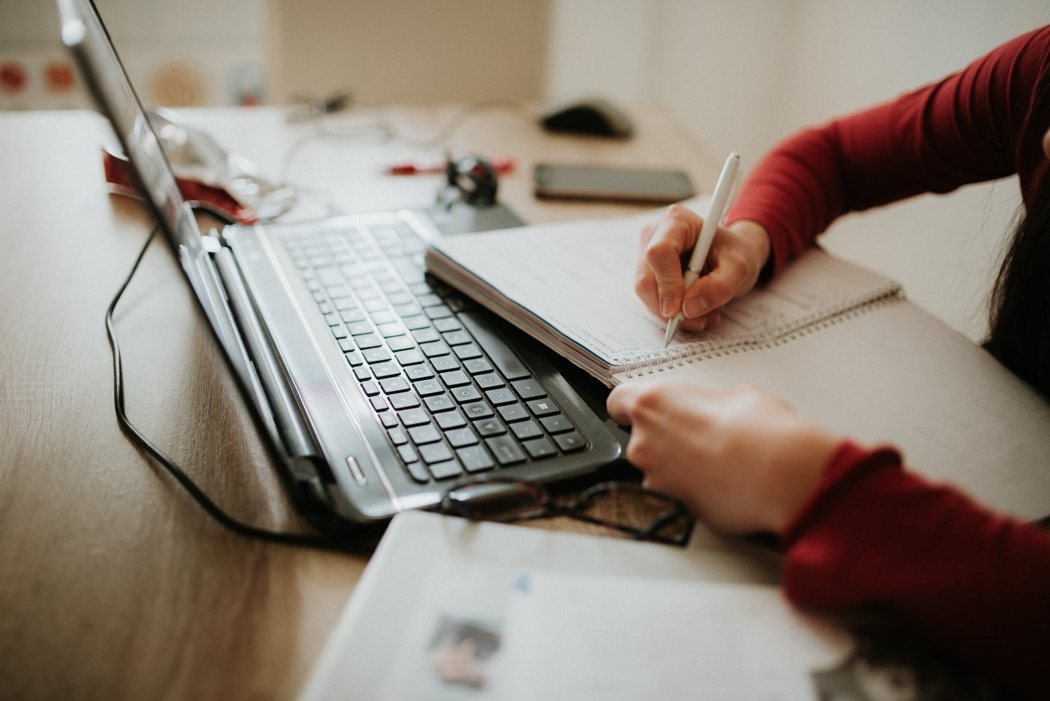 woman writing in a notebook with laptop nearby