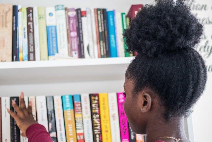 young black girl looking at bookshelf