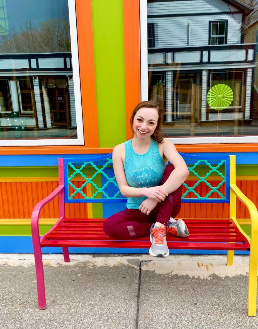 Camryn posing on a colorful bench in front of a vibrant building