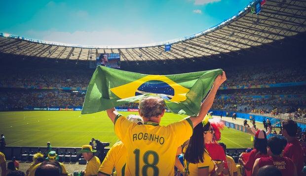 Man Raising Brazil Flag at Soccer Game
