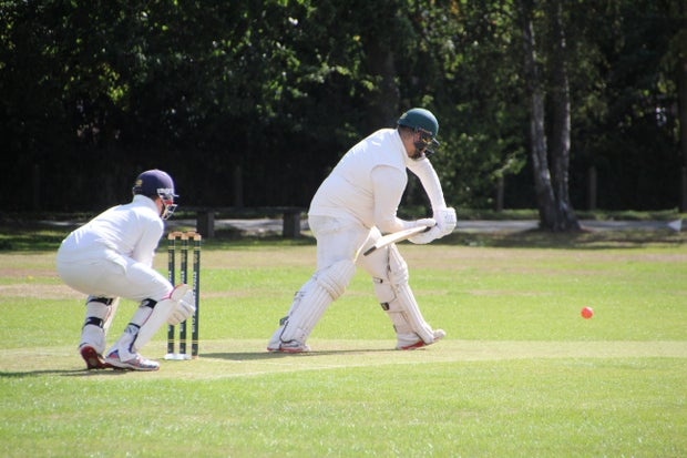 two men in white playing the sport cricket