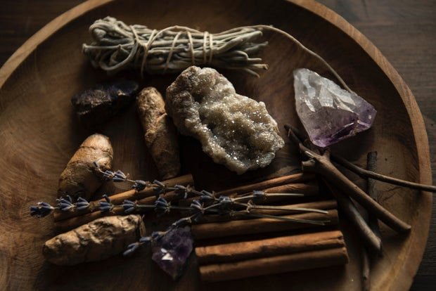 crystals and herbs on a wooden plate