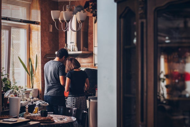 A man and woman standing in front of a oven cooking.
