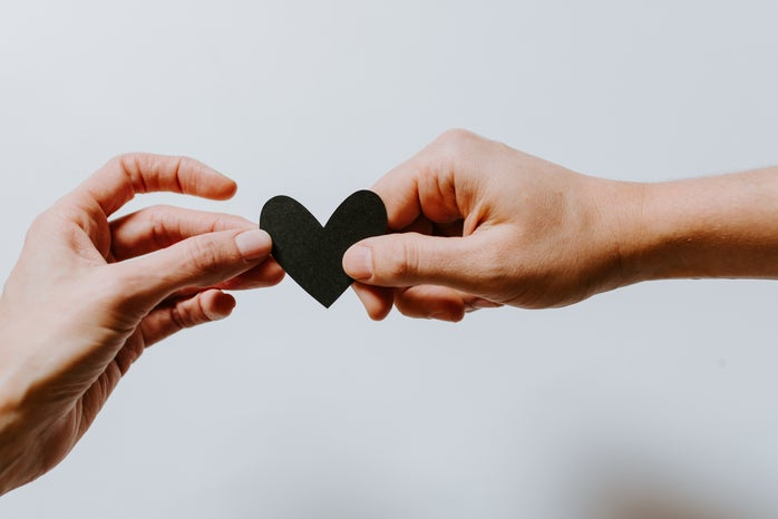 Two hands passing a paper heart to each other. The paper heart is black.