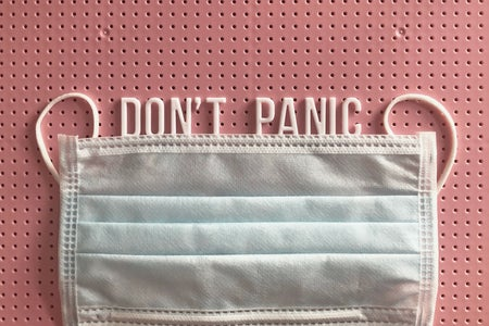 "mask on a pink letterboard with the words ""don't panic"" written"