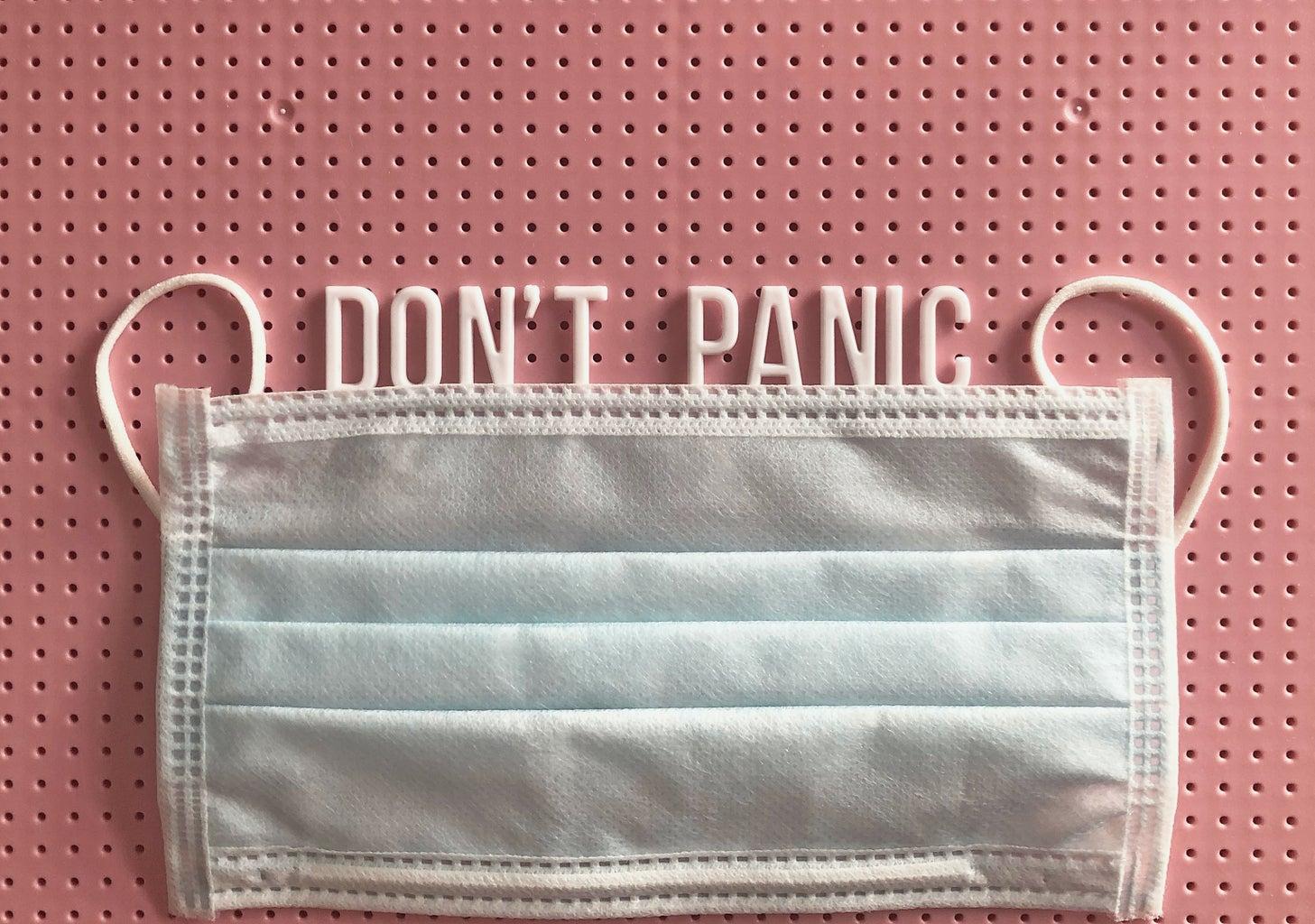 """mask on a pink letterboard with the words """"don't panic"""" written"""