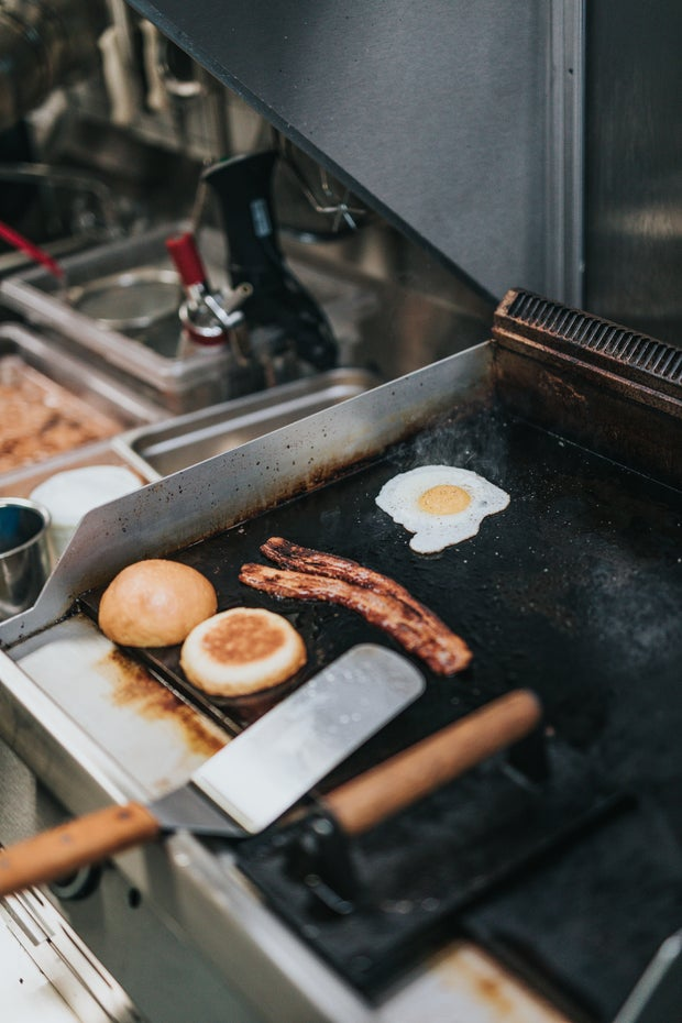 egg bacon and english muffin on a grill