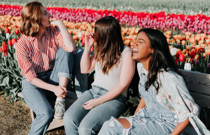 Three women talking with flowers