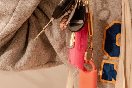 someone in sjsu sweatshirt holding up keys and pepper spray