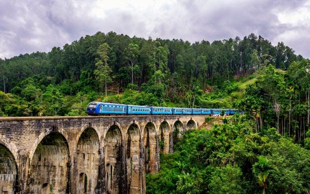 blue train surrounded by trees photo in Ella, Sri Lanka