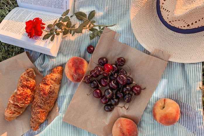 a picnic blanket set with cherries and pastries