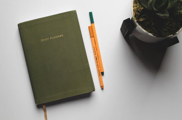 green book beside orange and white pen photo