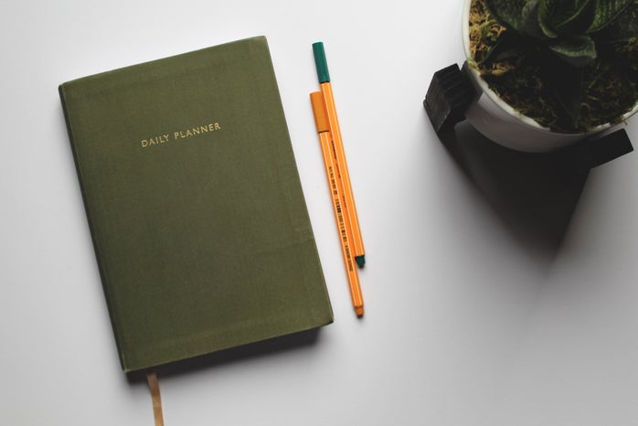 green book beside orange and white pen photo