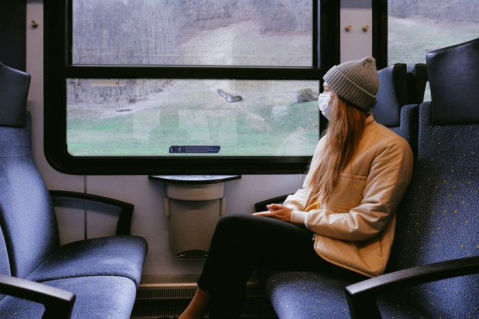 Woman sitting on a train with a beanie and mask on looking out the window.