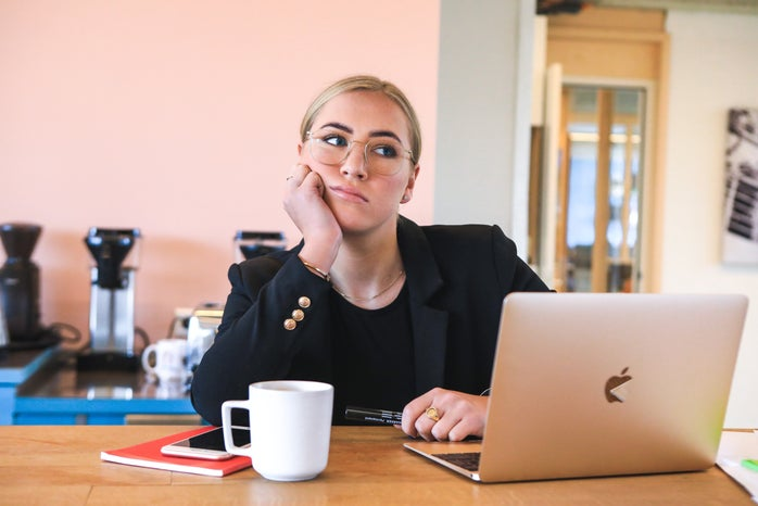 Woman sitting at desk with laptop and coffee looking bored