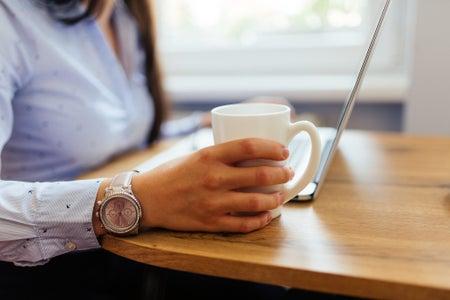 Woman wearing watch holding coffee mug while at laptop