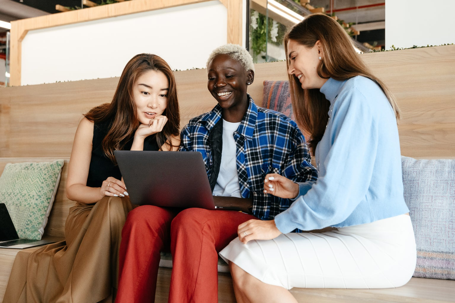 Multiracial cheerful women browsing laptop together