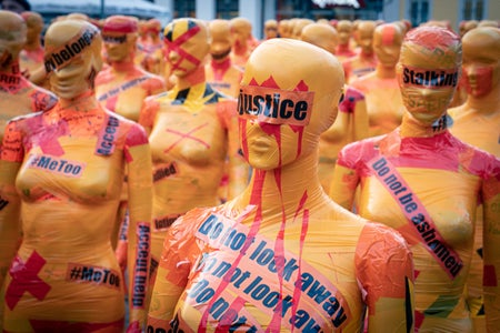 Mannequins covered in paint and tape with words such as 'justice' written on them