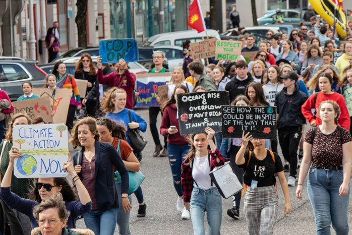 crowd of people marching at a climate change rally