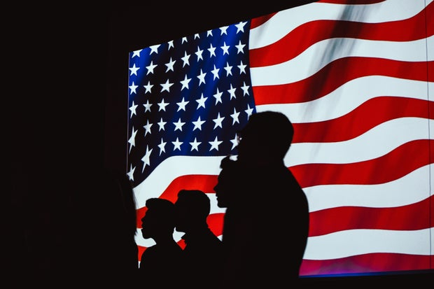 Four silhouettes stand in front of a digital American flag