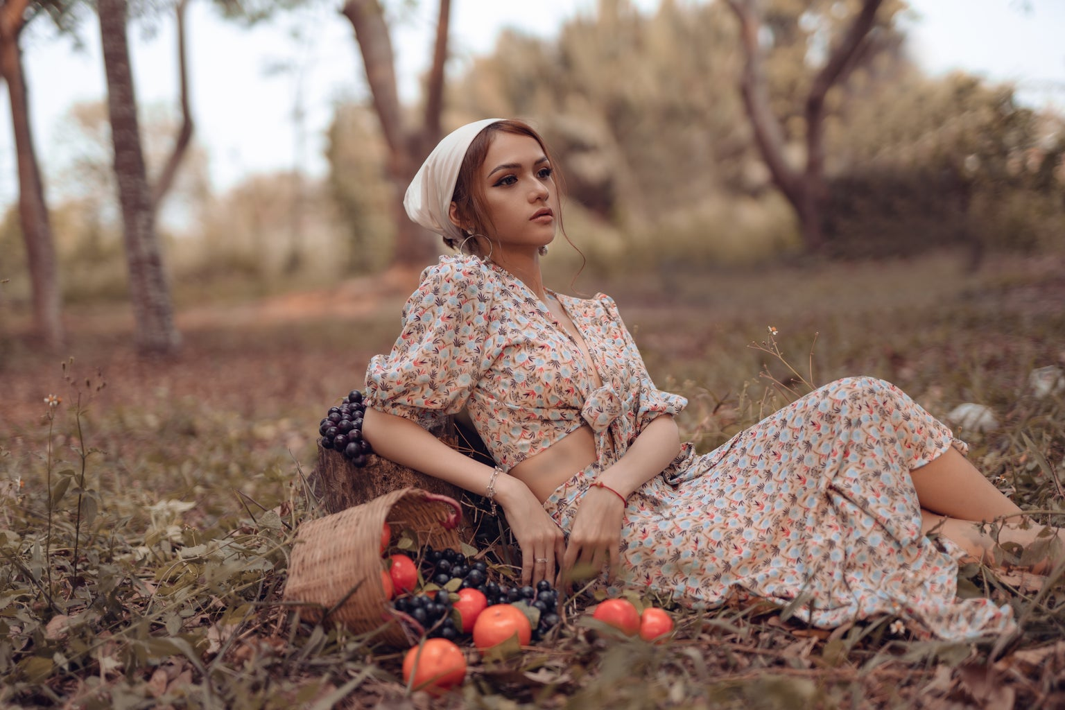 A girl sit in a forest with fruits