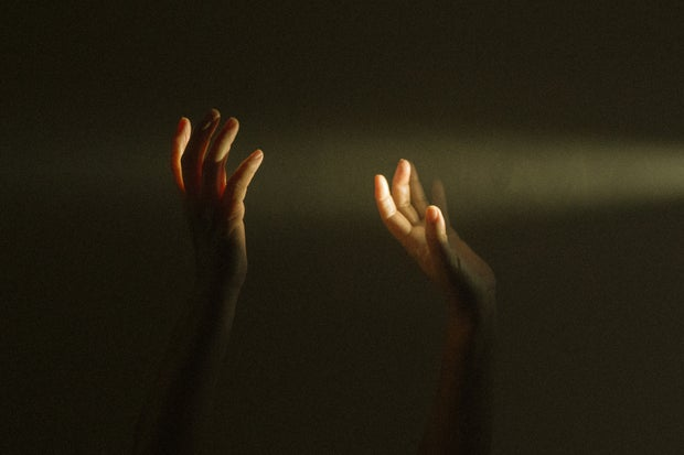 person raising their hands in a sunlight beam