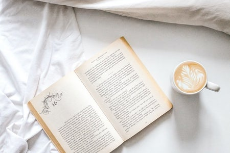 book with latte in bed