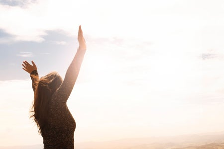 woman holding arms up to sunshine