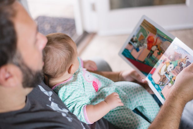 Father reading a book to his baby