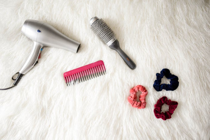 Grey hair dryer near pink comb and scrunchies