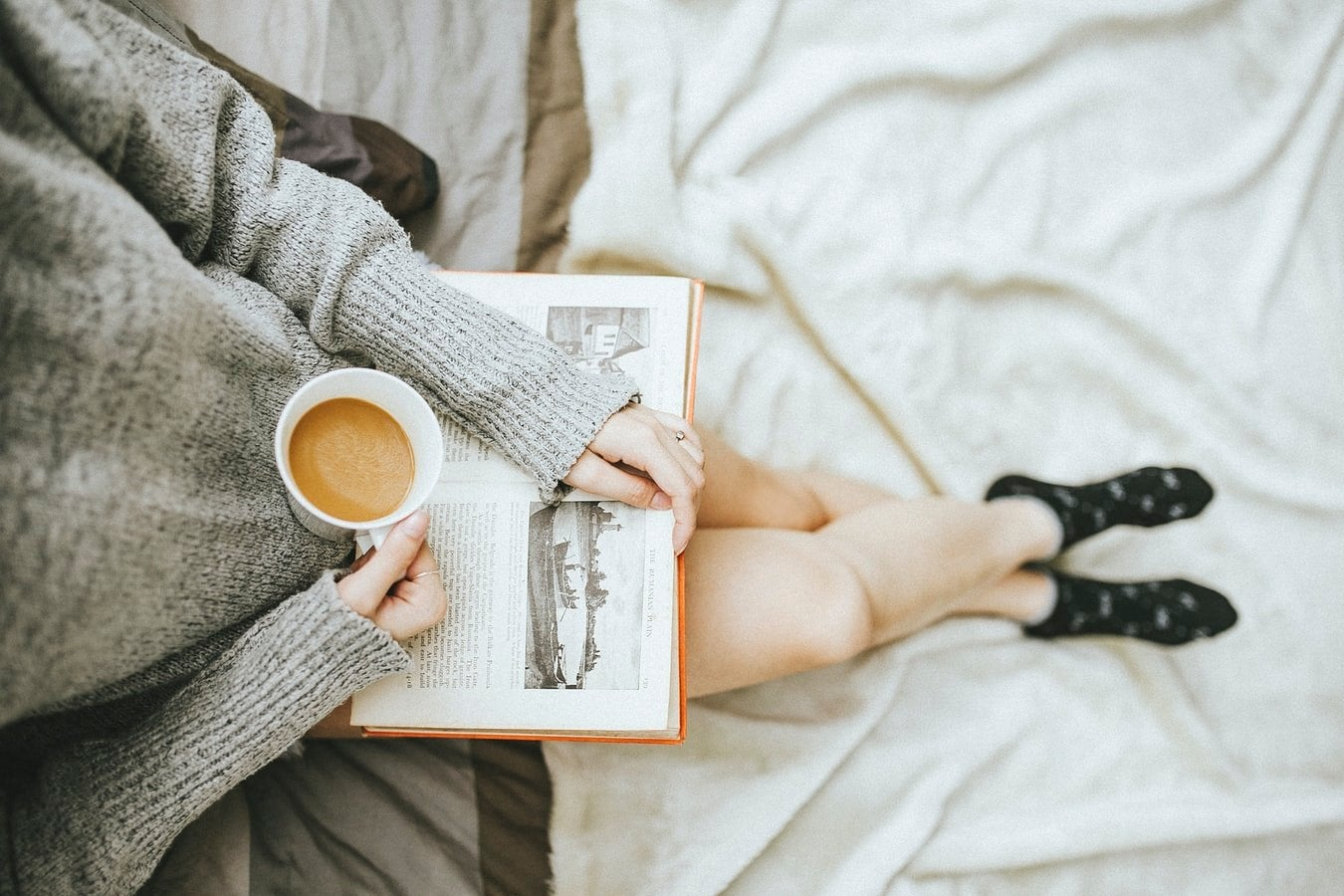 woman holding cup of coffee and reading a book while sitting on bed