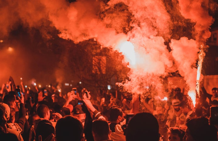 Anonymous people standing amongst smoke at riot at night