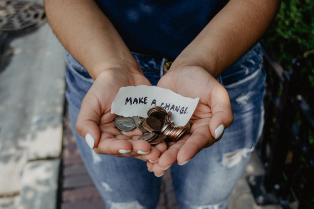 person holding coins and paper note in hands