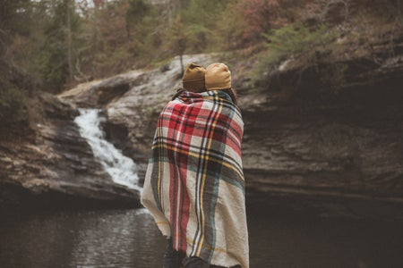 two people standing together under a blanket near a body of water